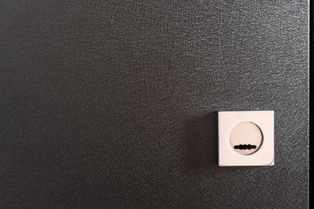protector lock on black metal door, home security close up.