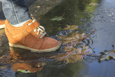 woman feet walking in a puddle in orange boots.
