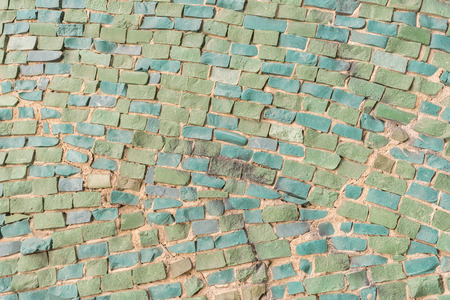green Surface of old crumbling abstract decorative mosaic as background. Multicolored ceramic stones on wall building.