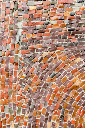 red Surface of old crumbling abstract decorative mosaic as background. Multicolored ceramic stones on wall building.