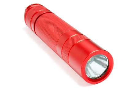 Red led pocket torch light isolated on white background. Modern tactical waterproof flashlight.