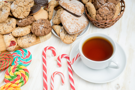 Sweet cookies, candys and a mug of tea on a white wooden table.