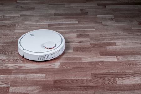 White robotic vacuum cleaner runs on laminate floor. Robot controlled by voice commands for direct cleaning. Modern smart appliance for cleaning house.