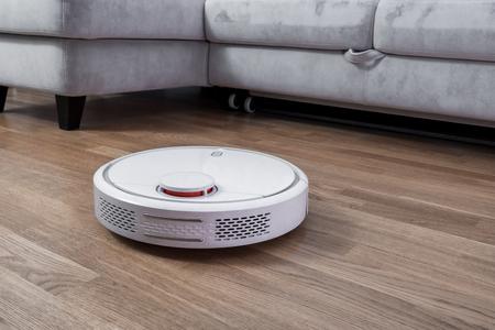 La aspiradora robótica corre cerca del sofá en la habitación en el piso laminado. Robot controlado por comandos de voz para limpieza directa. Servicio de limpieza de tecnología de limpieza inteligente moderna.