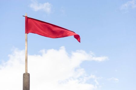 narrow red swinging flag on wooden flagpole against sky.