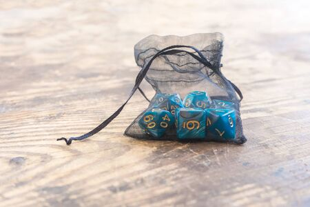 close up set of blue color dice for many role playing games on wooden table. Stock Photo