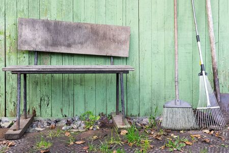 Empty dirty garden shovel, broom and rake stay near old weathered bench against wooden wall. Banco de Imagens