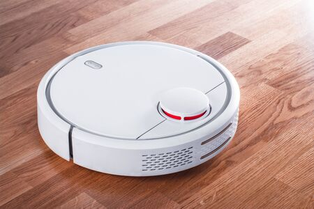 white robotic vacuum cleaner in rays of morning sun. robot controlled by voice commands for direct cleaning. modern smart appliance for cleaning house.