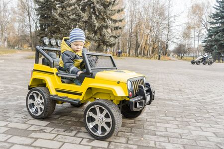 toddler with enthusiasm study control of yellow children car with an electric motor in autumn city Park.