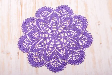 Vintage crocheted round doily with violet pattern on light wooden background. Top view. Decoration of interiors.
