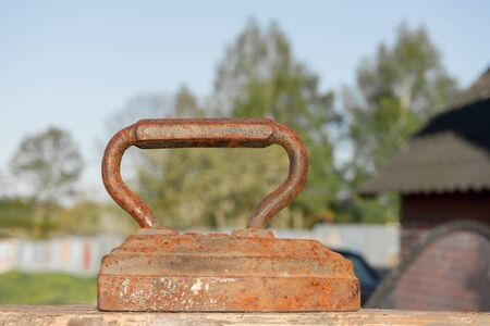 Old rusty Vintage iron with big corroded handle for ironing. Antique household item on sunny day.