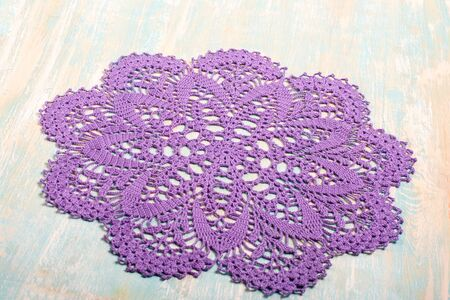 Vintage crochet round purple cotton lace doily with delicate ornament on light wood background. Needlework. Concept of self-development. Hobbies in free time.
