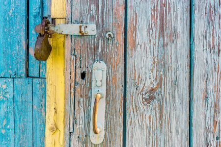open iron padlock on a battered wooden door with weathered cracks of blue and yellow colors of old country house.