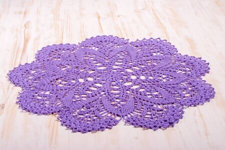 Vintage knitted round purple cotton napkin with elegant ornament on a light wooden background. Ancient tradition. Concept of interior design and a cozy home.