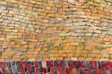 surface of old crumbling abstract decorative mosaic with orange and red colors as background. Multicolored ceramic stones on wall building. With place for text.