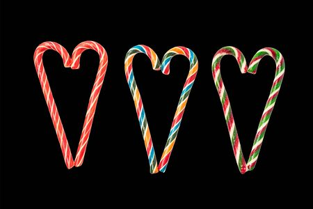 Colorful candy canes are laid out in shape of heart. Isolated on black background. Traditional holiday treat. Sweet candies, confectionery.