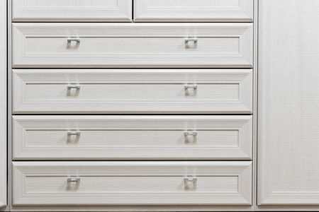 part of facade of wooden dresser, modern design chest of drawers, commode with four boxes, home storage system.