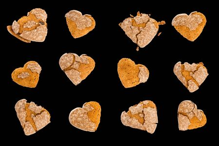 Stale, dry gingerbreads in shape of heart with cracked glaze with crumbs. Isolated on black background. Confectionery. Sweet pastries.