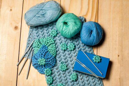 Composition of knitting tools and crocheted blue-green openwork napkins, balls of colored yarn, plastic grey hooks and book on wooden background. Concept of hobbies and crafts.