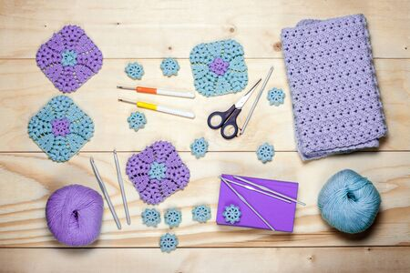 Composition of knitting accessories. Purple crocheted square napkins, balls of wool yarn, scissors, crochet hooks on light background of wooden boards close up view from top, flat lay.
