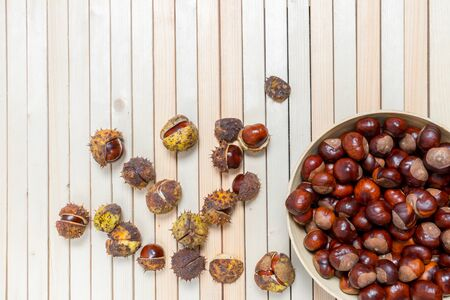 On light wooden background ripe chestnuts in prickly shells and bamboo plate filled with peeled nuts. Top view. Backdrop with copy space and place for text, design.