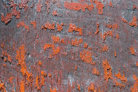 Fragment of old rustic wooden panel with badly peeling, cracked red paint on surface in close up.