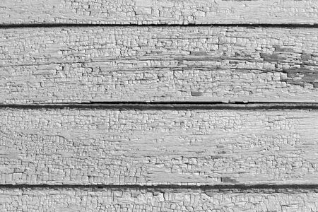Deep expressive cracks on wooden boards of house wall with old cracked weathered gray paint close up. Abstract pattern as background for your design, blank template.