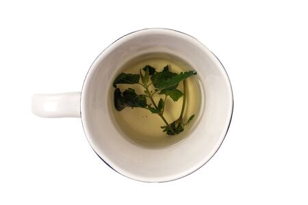 Fresh herbal tea made from green Melissa leaves in a ceramic mug isolated on white. Healing, homeopathic drink. alternative medicine.