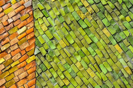 Decorative smalt mosaic on wall of building. Orange and green abstract, geometric background for your design with copy space and place for text. Minimal concept.