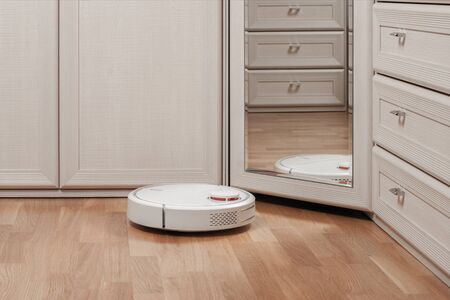 reflection of white robot vacuum cleaner running before mirror in bedroom. modern smart appliance for cleaning house. Banco de Imagens