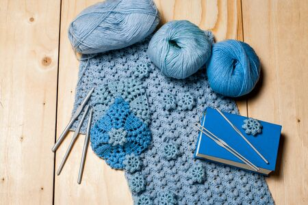 On wooden background elements of crochet, knitted blue lace napkins and knitting tools, balls of yarn and hooks. Hobbies in free time.