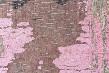 Fragment of old wooden panel with peeling pink paint on surface and small cracks clogged with dry river sand closeup. Grunge texture background for your design. Imagens