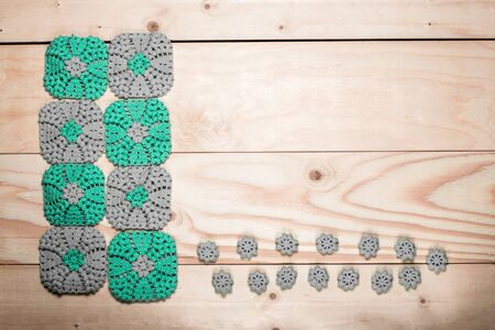 Crocheted gray-green square napkins with elegant pattern on background of light wooden table close up with space for text. Knitting. Elements of craft to left. DIY concept.