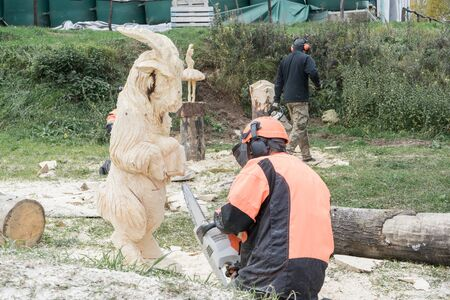 Woodcarver in special suit and headphones creates wooden sculpture of sheep with chainsaw. Hobbies in your free time.