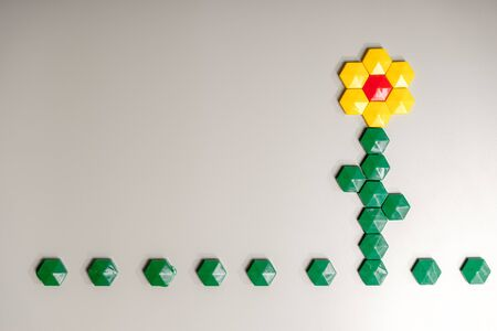 Flower made from children's mosaic, magnets on iron surface for your design with copy space and place for text. Leisure of child, development of fine motor skills and abstract thinking.