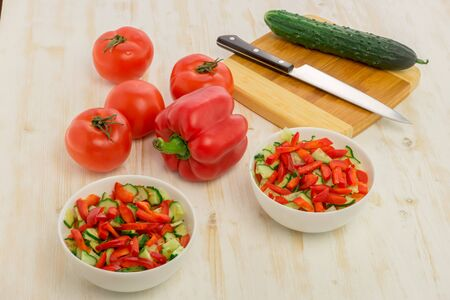 White bowls with fresh salad of green cucumbers, red tomatoes and bell peppers on light wooden surface. Vegetables. Lowcalorie vitamin dietary food. Concept of healthy lifestyle.