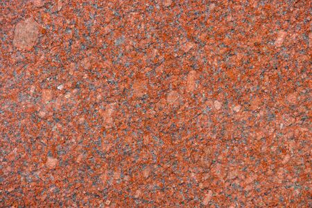 Imperial Red granitic - natural drawing of stone surface of rich red color with fine-grained structure of cold color scale. Polished granite tile.