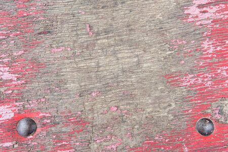 Old worn cracked surface of wood plywood with peeling red paint and iron nails. Abstract textured background with copy space and place for text.