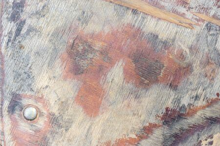 Flooring is made of wooden plywood with weathered and cracked surface with iron nail. Abstract textured background closeup for your design. Imagens