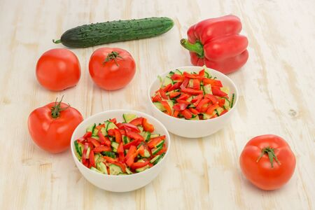 Fresh salad of sliced green cucumbers, red tomatoes and bell peppers on wood table. Vegetables. Gluten-free, lactose-free vegan food.