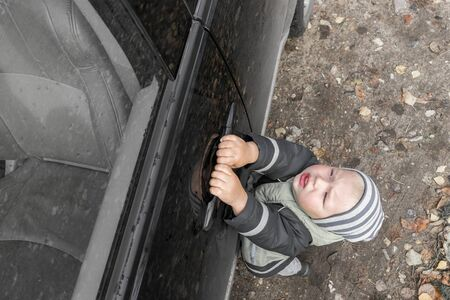 Cute little blond boy in striped hat struggles to open door of black, dusty car, hanging on handle. Family travel. Imagens