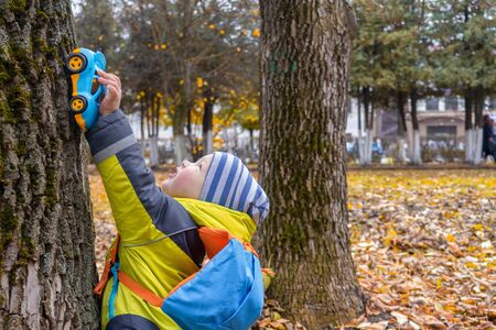 Little boy in yellow jacket, striped hat, with backpack plays with blue toy car on trunk of old tree in city Park in autumn. Concept of child development. Games and entertainment with baby. Imagens