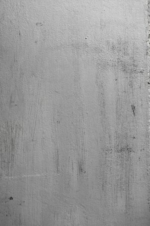 Concrete texture of wall with rough surface painted in silver color with sharp brushstrokes and unpainted areas. Abstract vertical background.