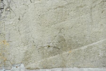 Fragment of texture of concrete wall of building with old cracked plaster with damp moldy cracks. Abstract background. Empty space.