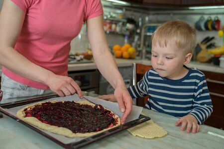 Little cute blond boy watches with curiosity as his mother spreads jam on dough for baking berry pie. Joint family cooking at home. Imagens
