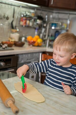 Little cute blond boy in kitchen is learning to cut flour dough with children's shaped baking knife. Concept of family leasure.