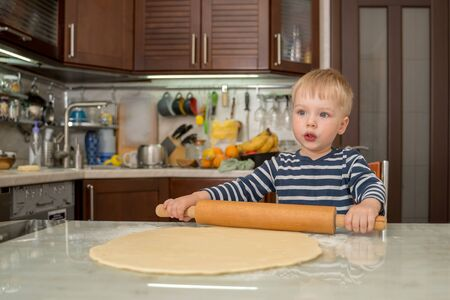 Little cute blond boy in kitchen prepares pie dough by rolling it out on table with rolling pin.