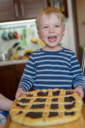 Little cute blond boy with happy smile enjoys baked berry pie with wild berry jam. Concept of happy childhood. Imagens