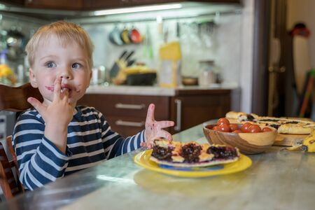 cute blond boy licks sweet fingers while eating a delicious homemade berry pie in the kitchen. Tasty food for kids. Imagens