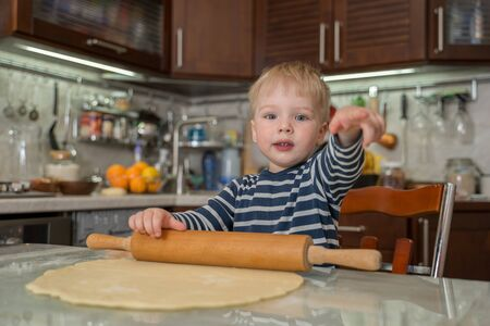 Little helper rolls out dough with rolling pin. Boy helps his mother in cooking in kitchen. Imagens